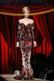 Gigi Hadid showed off her supermodel figure in a form-fitting patterned gown while walking the Moschino runway.