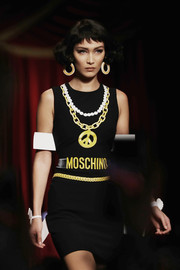 Bella Hadid showed off a cute tank dress printed with a pair of necklaces and a chain belt during the Moschino fashion show.