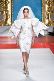 Gigi Hadid looked like a flamboyant bride in a white off-the-shoulder dress with oversized bow sleeves at the Moschino Spring 2020 show.
