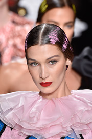 Bella Hadid walked the Moschino runway wearing a slick, pink-streaked chignon.