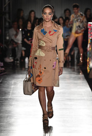 Jasmine Sanders walked the Moschino runway wearing a trenchcoat featuring a whimsical print that gave it a fun twist!