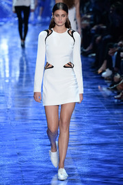Taylor Hill looked futuristic in a little white dress with shoulder and waist cutouts while walking the Mugler show.