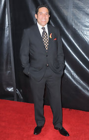 Oscar posed confidently at a Golden Globes after-party in an elegant black suit and checkered tie.