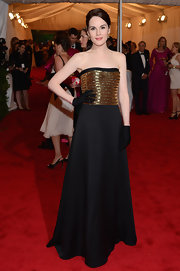 Michelle Dockery looked glam with ankle-length gloves and a gold-emblazoned dress at the Met Gala.