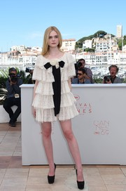 Elle Fanning went the ultra-girly route in a bow-adorned, tiered LWD by Chanel at the Cannes photocall for 'The Neon Demon.'