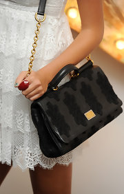 Pixie Lott paired her white lace dress with this black bag by Dolce & Gabbana. The black lace and leather bag featured chain detailing in gold.
