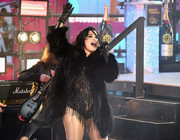 Demi Lovato teamed black leather gloves with a fur coat and a fringed bodysuit for a New Year's eve performance.
