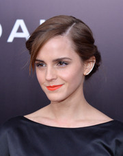 Emma Watson swiped on some bright orange lipstick for a radiant beauty look.