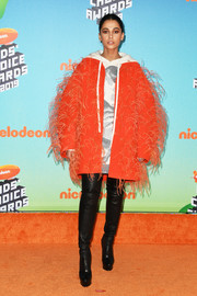 Naomi Scott layered a feathered orange coat over a hooded dress, both by Valentino, for the 2019 Kids' Choice Awards.