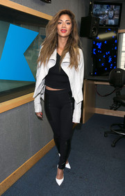 Nicole Scherzinger layered a white leather jacket over a black crop-top for an edgy-sexy look during her Kiss FM visit.