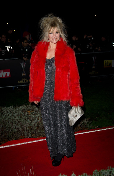 Jo wears a vivacious red fur coat over a silver gown.