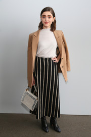 Natalia Dyer paired a striped maxi skirt with a plain white top for the Noon by Noor fashion show.