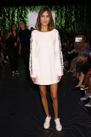 Alexa Chung hid her slim figure under a loose white Noon By Noor mini dress with long, embellished sleeves when she attended the label's fashion show.