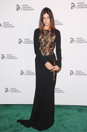 Julia Restoin-Roitfeld paired her sexy dress with a black YSL suede clutch.