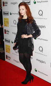 Olivia dons a sequins blazer over a loose black dress and tights.