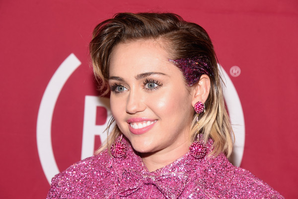 Miley Cyrus matched her sparkly pink outfit with a pair of dangling spheres.