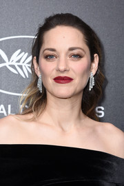 Marion Cotillard swiped on some red lipstick for a pop of color to her dark outfit.