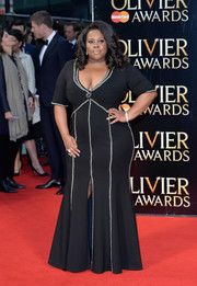 Amber Riley put her curves on display at the Olivier Awards in a plunging black mermaid gown with silver trim.