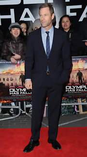 Aaron Eckhart chose a deep navy suit with a matching striped tie for his red carpet look at the London premiere of 'Olympus Has Fallen.'