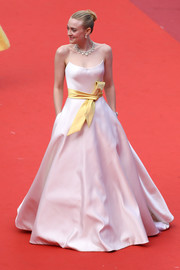 Dakota Fanning looked sweet and elegant in a strapless blush ballgown with a yellow sash at the 2019 Cannes Film Festival screening of 'Once Upon a Time in Hollywood.'