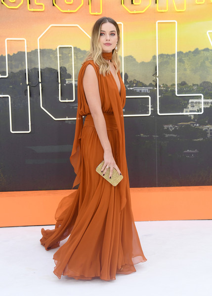Margot Robbie paired a gold Edie Parker clutch with a burnt-orange gown for the UK premiere of 'Once Upon a Time in Hollywood.'