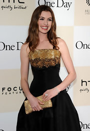 Anne Hathaway shined in an Alexander McQueen frock at the 'One Day' premiere. She paired the look with a beaded gold clutch and loose waves.