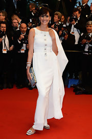 Ines de la Fressange looked elegant and sophisticated in a column-style white gown and matching cape.
