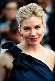Sienna Miller complemented her updo with a pair of Atelier Swarovski dangling earrings.