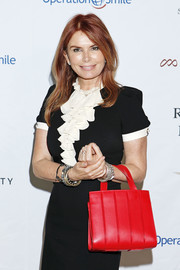 Roma Downey brightened up her monochrome dress with a red leather tote when she attended Operation Smile's Celebrity Ski & Smile Challenge.