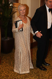 Judi Dench attended the British Academy Film Awards in a floor length cream colored dress that showcases her regal personality.