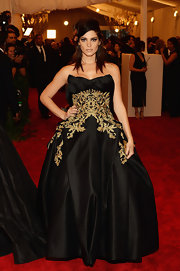 Ashley Greene opted for a totally dramatic red carpet look at the Met Gala when she chose this black strapless gown that featured gold embellishments along the bodice and skirt.