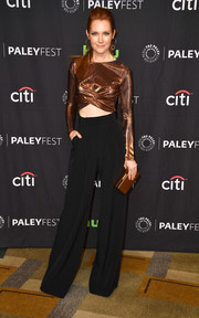 Darby Stanchfield matched her top with a gold box clutch by Edie Parker.