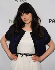 Zooey Deschanel covered up her sweet bow-belted dress with a cropped blue and green jacket.