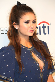 Nina Dobrev contrasted her youthful hairstyle with sexy smoky eye makeup.