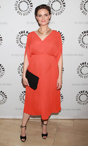 Emily Deschanel teamed her empire waist orange frock with black ankle strap wedges.