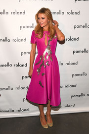 Paris Hilton kept it youthful and sweet in a leaf-embellished fuchsia dress by Pamella Roland during the label's fashion show.
