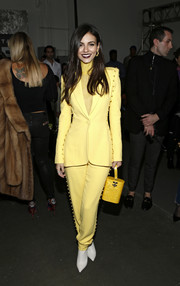 Victoria Justice matched her outfit with a yellow Edie Parker purse.