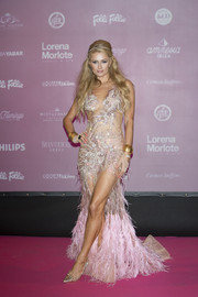 Paris Hilton complemented her gown with a pair of studded gold PVC pumps by Christian Louboutin.