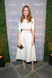 Darby Stanchfield topped off her trendy ensemble with a metallic gold clutch.