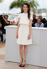 Astrid Berges Frisbey added contrast to her crisp white dress with red suede cutout peep-toes.