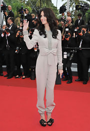 Paz Vega's eye-catching black satin rosette-adorned peep-toes were an unexpected choice for her dove gray jumpsuit.
