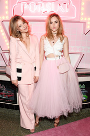 Suki Waterhouse tied her look together with a pink camera bag by Pop & Suki.