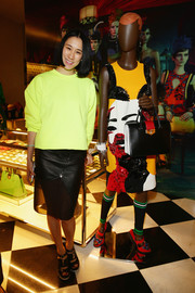 Eva Chen was sporty at the Prada Iconoclasts event in a yellow crewneck sweater.