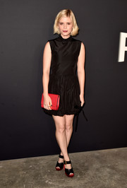 Kate Mara added a bright spot with a red leather clutch.