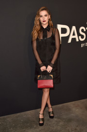 Zoey Deutch pulled her look together with a red and black leather tote, also by Prada.