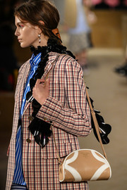 Kaia Gerber accessorized with a beige leather shoulder bag at the Prada Resort 2020 runway show.
