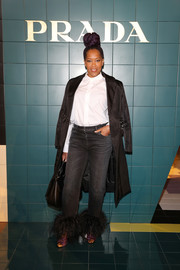 Regina King arrived for the Prada Spring 2020 show wearing a black duster coat over a white button-down and jeans.