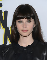 Felicity Jones' long dark locks looked sleek and mod cool when styled into a straight 'do with thick blunt bangs.