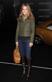 Maria bundled up for fall in a chic olive green jacket paired with dark brown leather knee-high boots.