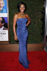 Teyonah dons a floor length strapless gown in a soft violet blue.